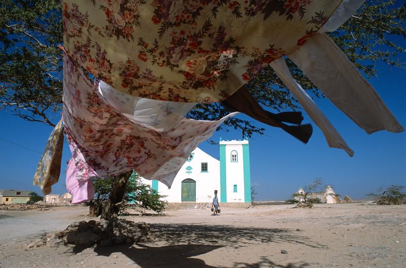Une femme portant trois sceaux d'eau devant la petite église de Rabil. Ile de Boa Vista/Cap-Vert