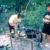 Glenis pours wines for the girls. Note hexamine stove on top of a steel dixie. Other dixie on table. Note full size VHS video recorder Panasonic AG-6400 with +/- lead to hookup to motorcycle battery for power ex solar panel on roof