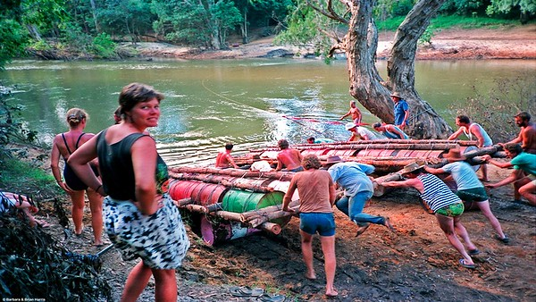 Launching heavy raft by rolling it on drums. Note guy acting as ballast on rear. Three days of hard work there.