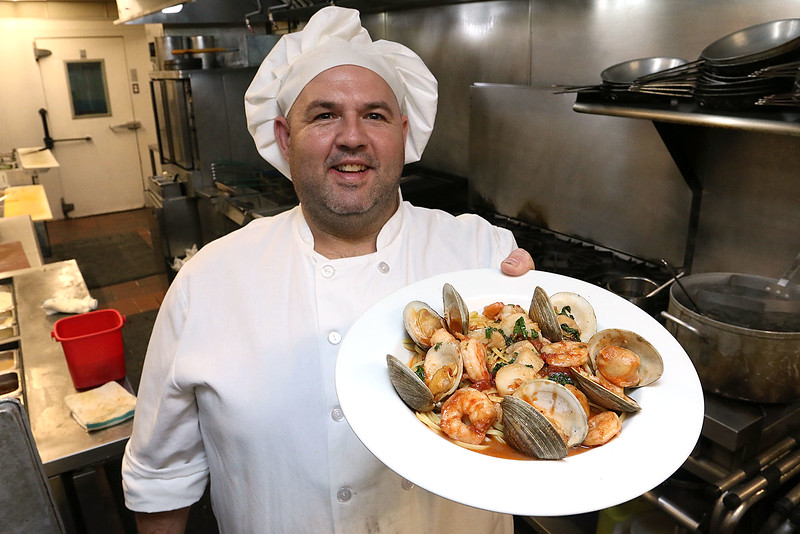 Capellini's Restaurant Kitchen Manager Jason Dubay shows off their seafood portofino, a sautéed shrimp, scallops, and littleneck clams in a spicy tomato aglio olio over linguini at the restaurant in Tewksbury on Wednesday afternoon. SUN/JOHN LOVE