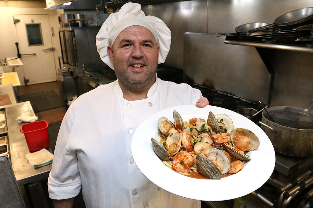 . Capellini\'s Restaurant Kitchen Manager Jason Dubay shows off their seafood portofino, a sautéed shrimp, scallops, and littleneck clams in a spicy tomato aglio olio over linguini at the restaurant in Tewksbury on Wednesday afternoon. SUN/JOHN LOVE