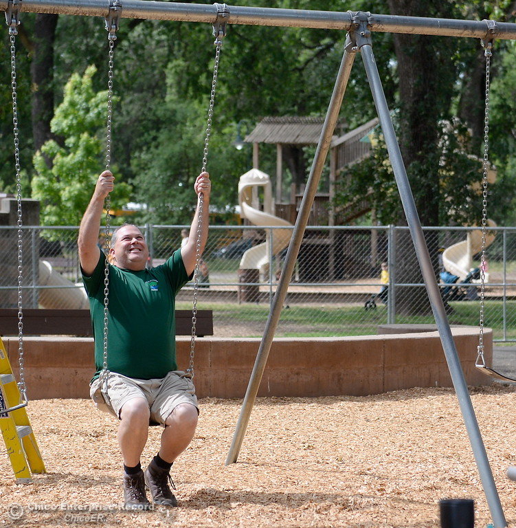 . Park Services Coordinator Shane Romain checks on one of the new swings while City of Chico workers put the finishing touches on the new swing section at Caper Acres Thursday May 10, 2018. New things include a bridge near the entrance, swings, a teeter totter and more. The new Swing Adventure Area Grand Opening is Saturday May 12 at 9:00 a.m.. (Bill Husa -- Enterprise-Record)