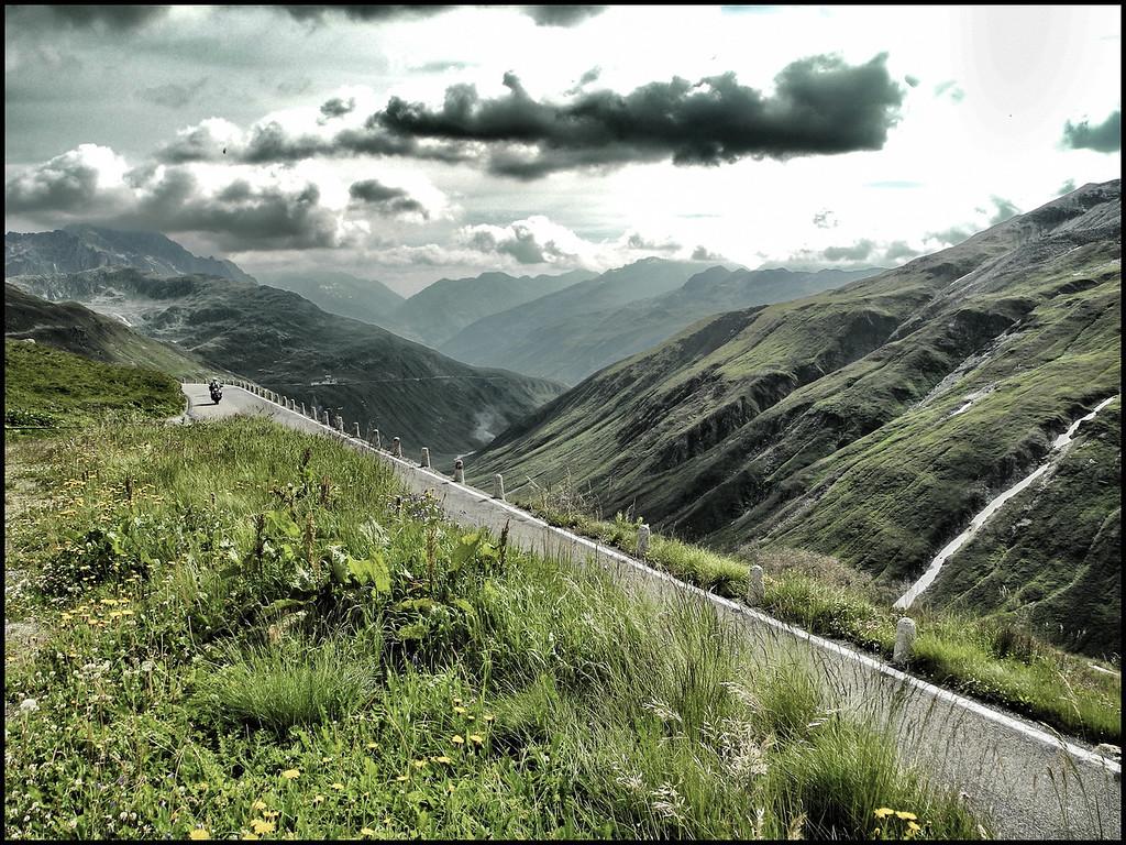 Jeudi 2 août 2012. Col de la Furka. Je jette un regard en direction de la descente du côté d'Uni et d'Hospenthal. La paysage est superbe. La moto qui arrive donne une petite idée de la largeur de la route au départ de la descente.