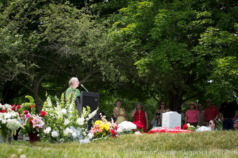 Flowers cover Dynaformer's grave as Sandy Hatfield, stallion manager at Three Chimneys speaking at Dynaformers memorial service.