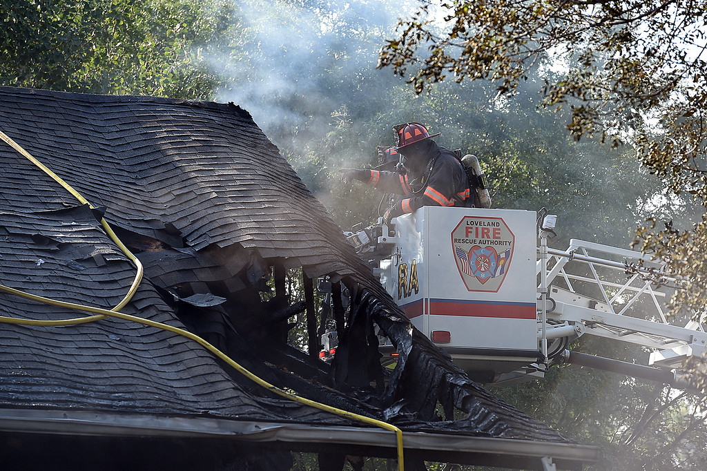 . Loveland Fire Rescue Authority firefighters work to extinguish a house fire caused when a car hit the house rupturing its electric and gas lines Wednesday, Sept. 6, 2017, at 202 Hopkins Ct. in Loveland. (Photo by Jenny Sparks/Loveland Reporter-Herald)