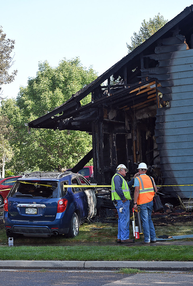 An Xcel Energy crew works at the scene of a house fire caused when a car hit the house rupturing its electric and gas lines Wednesday, Sept. 6, 2017, at 202 Hopkins Ct. in Loveland. (Photo by Jenny Sparks/Loveland Reporter-Herald)
