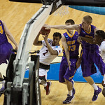 Quentin Snider (2) of the Louisville Cardinals drives to the basket while being defended by Wyatt Lohaus (33) and Nate Buss (14) of the Northern Iowa Panthers during the third round of the 2015 NCAA Men\'s Basketball Tournament at KeyArena on Sunday, Marc