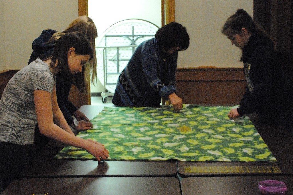 . Experienced volunteers offered guidance to high school students as they pinned fleece blankets in preparation for sewing. (Photos by Colleen Kowalewski)