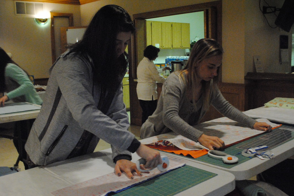. Students work together to measure and cut the fabric that will become pillow cases and care bags. (Photos by Colleen Kowalewski)