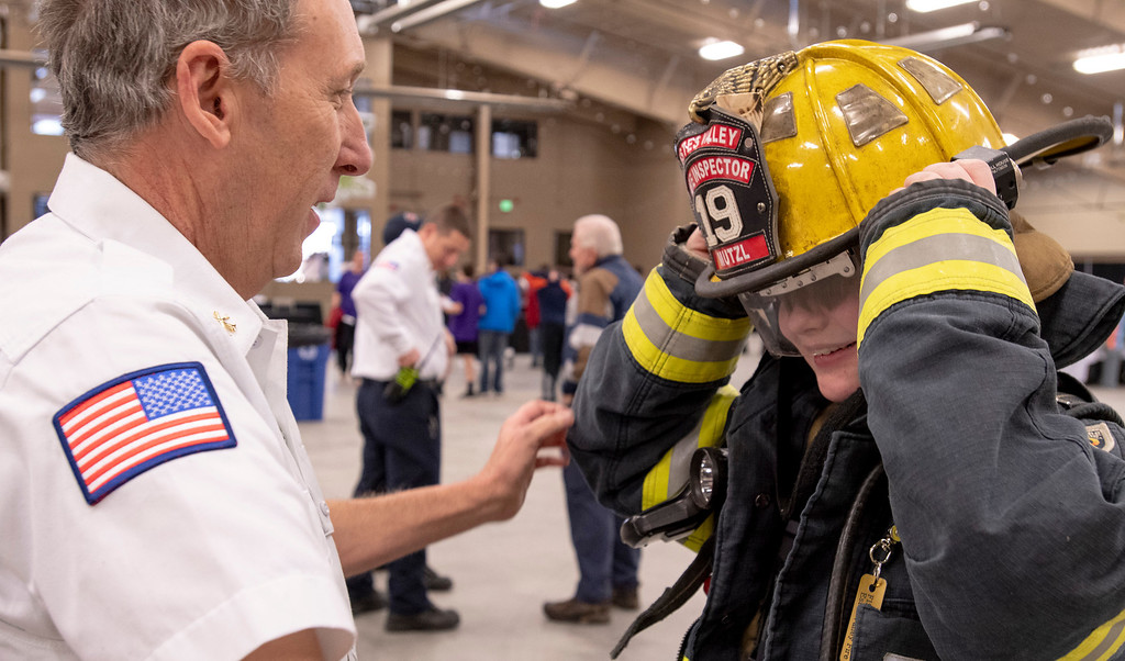 . Estes Valley Fire Prevention District Fire Marshal John Jerome helped out seventh graders at Estes Park Middle School try on a firefighter�s suit during their career fair on Friday, Jan. 25 at the Estes Park Events Complex.