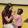 Student Ambassador Deven Samson entertains a little girl before Baccalaureate begins.