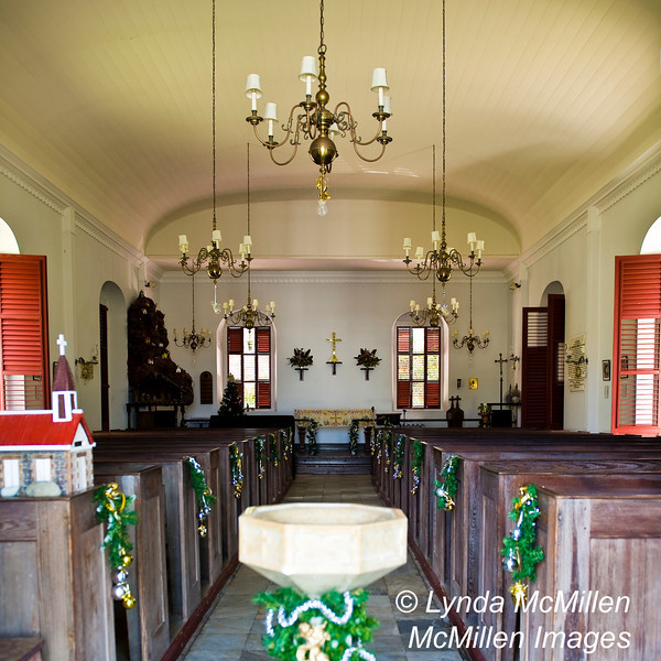 The original pine pews contrast with the white walls and marble floors.