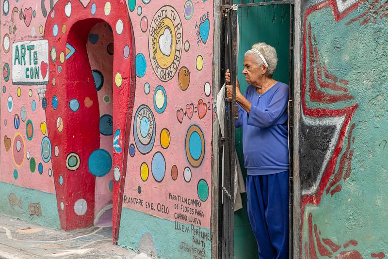 Old woman in colorful doorway.