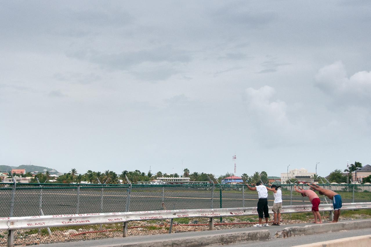 Tourists watch arriving planes in Princess Juliana International Airport