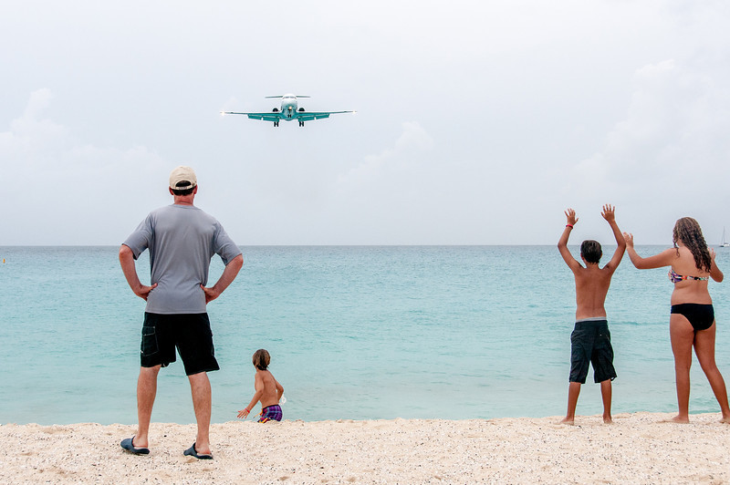 Tourists waving to approaching airplane in St. Martin