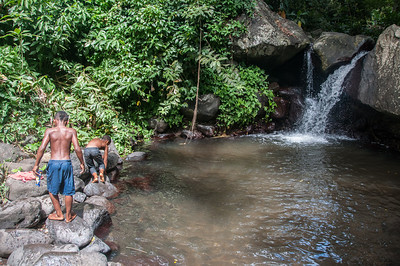 Boys swimming near a waterfall on the island of St. Vincent