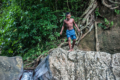 Boy jumping off rock to Waterfall at Wallilabou, St. Vincent