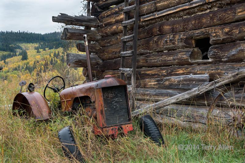 Abandoned tractor, log barn and wagon wheel, near Likely, British Columbia