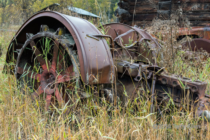 Old tractor wheel and engine block, near Likely, British Columbia