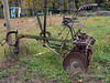 Antique 10-disk plow, side view, sitting by an electric fence, near Likely, British Colulmbia
