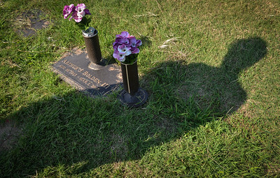 Cristal Terry visits the grave of her uncle, Arthur Bolden III recently at Highland Park Cemetery in Kansas City, Kansas.