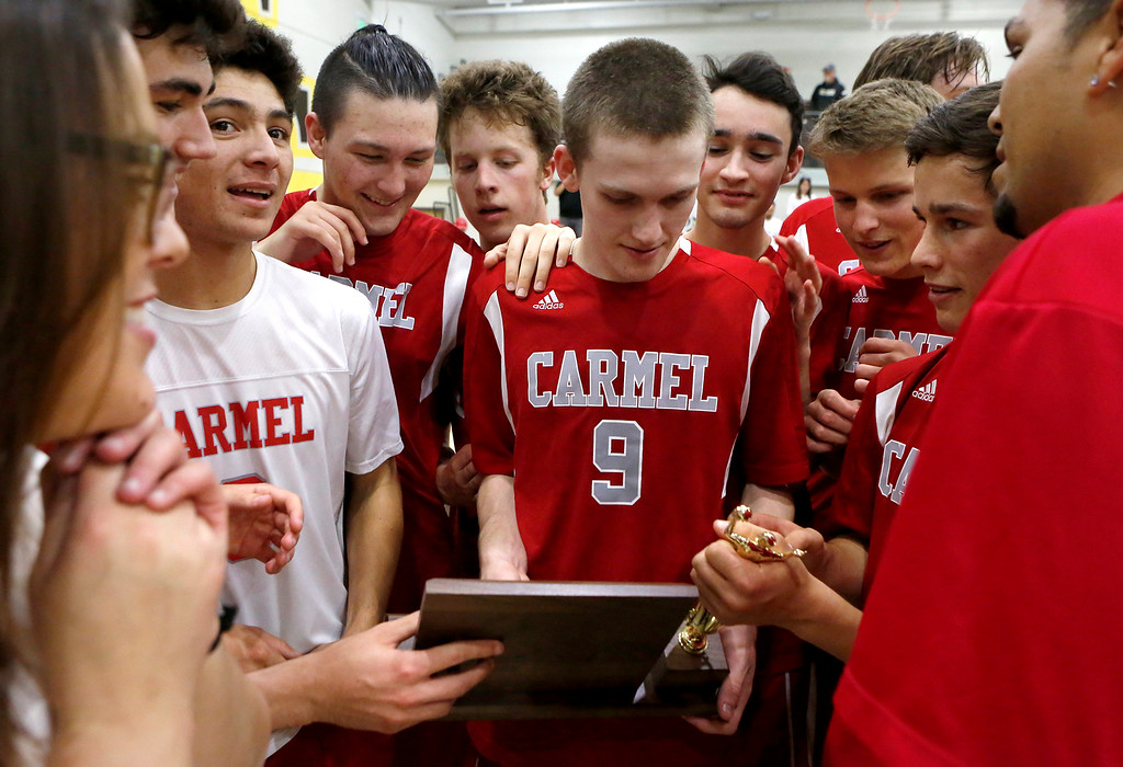 . Carmel players gather around the trophy after their win against  Harker during the CCS boys volleyball championship at St. Francis in Mountain View on Saturday May 12, 2018. Carmel won the match 3-2. (David Royal/ Herald Correspondent)