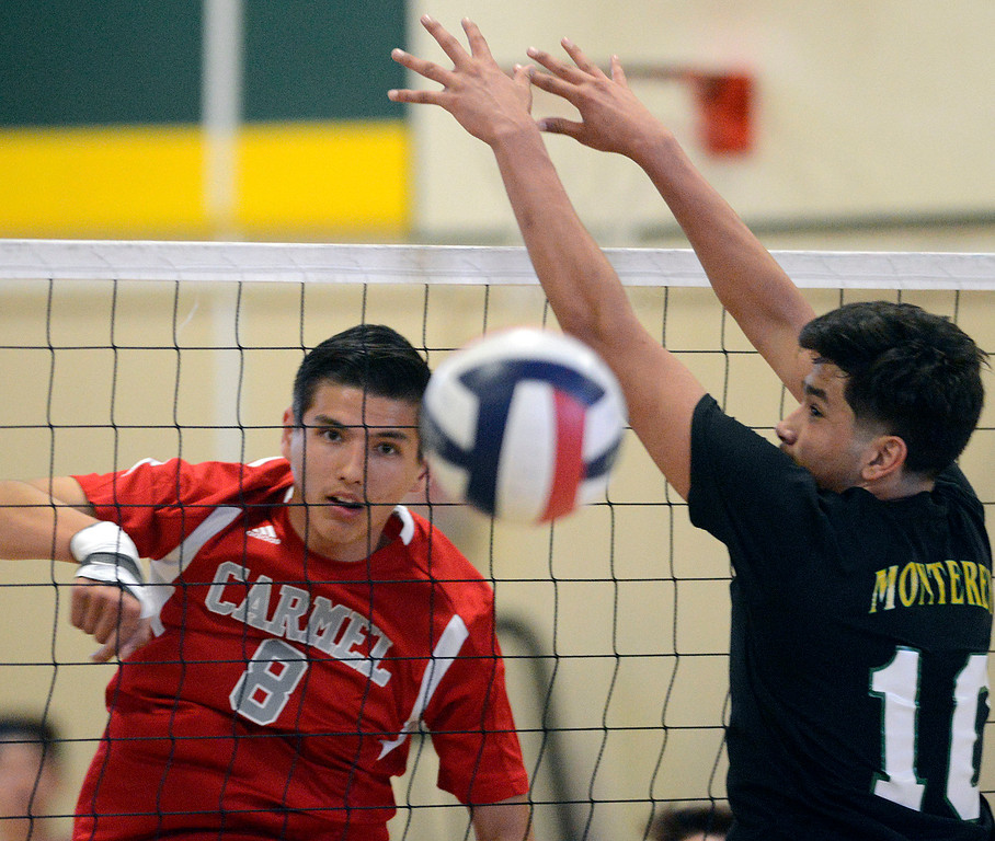 . Carmel\'s Alessandro Boreo hits the ball past Monterey\'s Juan Villar during boys volleyball in Monterey on Tuesday April 11, 2017. (David Royal - Monterey Herald)