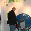 Dad and boy putting money into reimagine bank