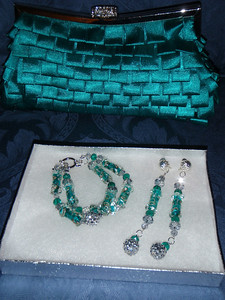 Jewelry and matching turquoise/silver clutch purse with silver link shoulder strap.
