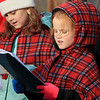 Theresa Letarte, 7, was watching some old Christmas movies and decided she wanted to go caroling. She talked her family and friends into doing it. Here she sings at one of the houses in her neighborhood. Just behind her is her friend Caylen St. George. SENTINEL & ENTERPRISE/JOHN LOVE