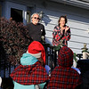 Theresa Letarte, 7, was watching some old Christmas movies and decided she wanted to go caroling. She talk her family and friends into doing it. her Rick Terrie Tranique listen to the kids as they sang on Saturday afternoon. SENTINEL & ENTERPRISE/JOHN LOVE