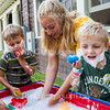 From left: Isabelle Dawson, five, Sam Durkee, five, teacher Tori Savage, and Gram Whitehead, five, wash off the shaving cream they had been playing with at 10 AM on July 18, 2016, outside of the Yellow Room at Children's School. Before participating in Children's School's Open House, the children and teachers in the Yellow Room did several activities, including playing with shaving cream, playing outside, and practicing the songs they would sing in the program. Photo by Carolyn Brown.