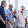 From left: Tom Hubbell, Dick Turney, and Jack Voelker clink wine glasses on July 23, 2016, at a gathering honoring the tenth anniversary of the Turney Sailing Center. Turney was the original donor to the Turney Sailing Center, and Hubbell is a former president of the United States Sailing Association. Photo by Carolyn Brown.