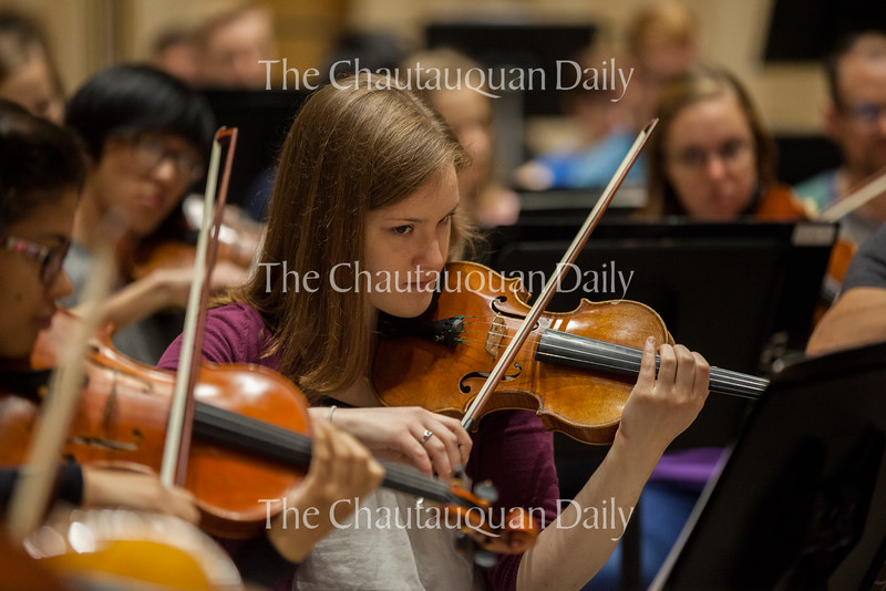"""Violinist Rachel Stenzel rehearses with the other members of the Music School Festival Orchestra in Lenna Hall on June 30, 2016. The entire MSFO will perform three pieces (Haydn's Symphony No. 2 in G Major, """"Oxford""""; Mark Edwards Wilson's """"The Phoenix""""; and Ravel's arrangement of Mussorgsky's """"Pictures at an Exhibition"""") at the Amphitheater on Tuesday, July 5, at 8:15 PM. Photo by Carolyn Brown."""