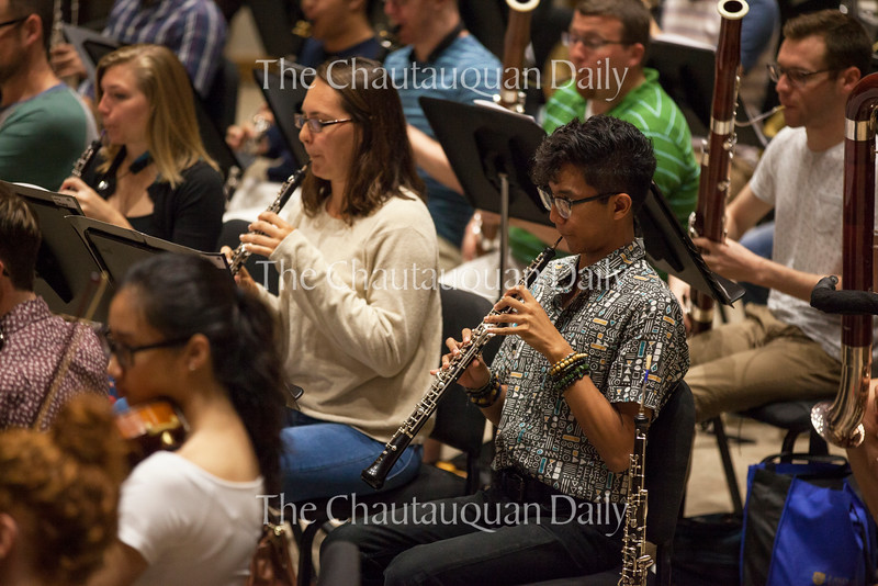 """Kevin Gupana plays his oboe during a rehearsal with the other members of the Music School Festival Orchestra in Lenna Hall on June 30, 2016. The entire MSFO will perform three pieces (Haydn's Symphony No. 2 in G Major, """"Oxford""""; Mark Edwards Wilson's """"The Phoenix""""; and Ravel's arrangement of Mussorgsky's """"Pictures at an Exhibition"""") at the Amphitheater on Tuesday, July 5, at 8:15 PM. Photo by Carolyn Brown."""