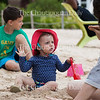 """As Jayden Greening, eight, left, watches other children swim in Chautauqua Lake, his cousin Iona Morris, fifteen months, center, reacts to her mother Mollie Worth, right, imitating a duck at Children's Beach. Greening, who was visiting Children's Beach with his mom and sister, is from California, but Morris and Worth are from London.<br /> <br /> Mollie Worth said that she prefers the culture, geography, and climate of Chautauqua to those of English seaside towns like Brighton. Referencing the United Kingdom's recent referendum to leave the European Union, Worth said that her family's trip to Chautauqua was """"[their] own personal Brexit.""""<br /> <br /> Photo by Carolyn Brown."""