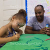 Chianti Lopez, 5, left, draws as her father Anibel Lopez, right, looks on at 11:30 AM on July 15, 2016, in the Blue Room at Children's School. Parents were encouraged to visit Children's School on Friday as part of its Open House event. Photo by Carolyn Brown.