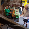 """Carolyn Benton, chimemaster of the Miller Bell Tower, left, plays the chimes as Jim Simmelink, right, looks over a list of songs that visitors to the Bell Tower can request Benton to play at 6 P.M. on Wednesday, August 24, 2016, in the Bell Tower. Simmelink chose """"When Irish Eyes Are Smiling."""" Photo by Carolyn Brown."""