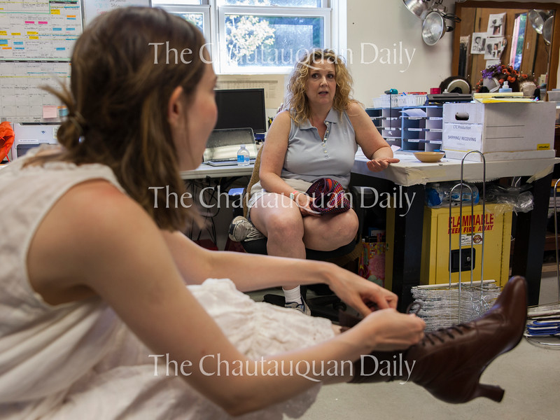 """In the costume shop of Brawdy Theater Studios on June 27, 2016, Allison Altman, left, puts on one of the Victorian shoes that her character Sabrina Daldry wears in Chautauqua Theater Company's production of """"In the Next Room (or the vibrator play)"""" while costume designer Tracy Christensen, right, discusses the costume with her. """"In the Next Room (or the vibrator play)"""" runs at Bratton Theatre from July 1 through July 10.<br /> <br /> Photo by Carolyn Brown."""