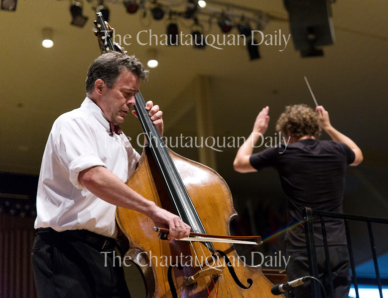 """Bassist Edgar Meyer, left, plays """"Concerto for Double Bass in D (1993)"""" as conductor Teddy Abrams, right, leads the Chautauqua Symphony Orchestra at their 8:15 PM concert on July 14, 2016, in the Amphitheater. Meyer, who composed the piece himself, returned to the stage for two encores after playing the piece. Photo by Carolyn Brown."""