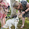 Barbara Delmont, left, stands with her poodle/terrier mix Scruffy as Rev. Lisa Marchal of the Methodist House, right, blesses him at the Blessing of the Animals gathering at 4 P.M. on Sunday, August 21, 2016, at Miller Park. Pet owners from around the grounds gathered for Chaplain Lisa Marchal of the Methodist House to bless their pets, some of whom were represented by photos on phones or in picture frames. Photo by Carolyn Brown.