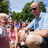 Dean Arnold, one, laughs while playing with his parents Sarah and Greg Arnold at the Chautauqua Community Band 25th Annual Independence Day Concert at 12:15 PM on July 4, 2016, on Bestor Plaza. The Arnold family enjoyed a picnic on Bestor Plaza while listening to the concert.<br /> <br /> Photo by Carolyn Brown.