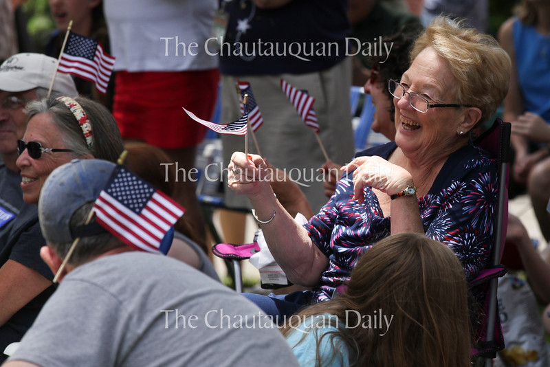 """Donna Downey smiles while waving a flag that Chautauqua Community Band conductor gave her as the band played John Philip Sousa's """"The Stars and Stripes Forever"""" at their 25th Annual Independence Day Concert at 12:15 PM on July 4, 2016, on Bestor Plaza. Many members of the audience  clapped and waved American flags during the tune.<br /> <br /> Photo by Carolyn Brown."""
