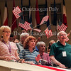 "Left to right: Susan Laubach, Lee Heinz, and Nelson Helm enjoy the music of ""The Stars and Stripes Forever"" as people wave flags at the conclusion of the  Chautauqua Symphony Orchestra's Independence Day Pops Celebration concert at 10 PM on July 4, 2016, in the Amphitheater."