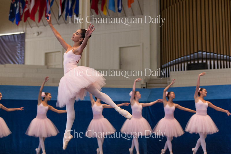 """Esme Cosgrove, center, leaps across the stage in a piece entitled """"Cinderella at the Ball,"""" choreographed by Maris Battaglia, Associate Artistic Director of the School of Dance, in the Chautauqua Dance Student Gala at 2:30 PM on July 17, 2016, in the Amphitheater. The show featured the Chautauqua Festival and Workshop Dancers from the School of Dance. Photo by Carolyn Brown."""
