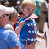 Riley Rogers, right, celebrates the Fourth of July with his mother Megan Rogers during the Chautauqua Community Band 25th Annual Independence Concert at 12:15 PM on July 4, 2016, on Bestor Plaza. Many children attended the concert, and some even participated in a special children's parade led by conductor Jason Weintraub near the end of the concert.<br /> <br /> Photo by Carolyn Brown.
