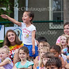 Siena Pahls, 6, stands up to wave to her mother as parents arrive to hear their children sing at the Open House at 11 AM on July 15, 2016, at Children's School. Children sang three different songs for parents before proceeding to their classrooms to do crafts and skits. Photo by Carolyn Brown.