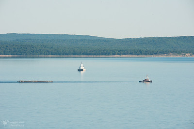 Tug Zeus glides north on Manitou Passage by the Crib Lighthouse