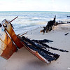 Burned out boat  on beach with people swimming  in background