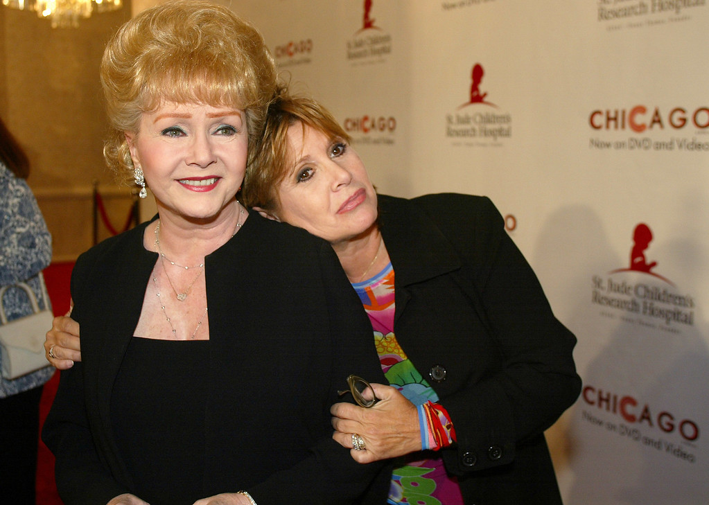 ". FILE - In this Tuesday, Aug. 19, 2003 file photo, Debbie Reynolds and Carrie Fisher arrive at the ""Runway for Life\"" Celebrity Fashion Show Benefitting St. Jude\'s Children\'s Research Hospital and celebrating the DVD relese of Chicago in Beverly Hills, Calif. On Tuesday, Dec. 27, 2016, a publicist said Fisher has died at the age of 60. (AP Photo/Jill Connelly, File)"